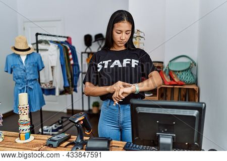 Young hispanic woman working as staff at retail boutique checking the time on wrist watch, relaxed and confident
