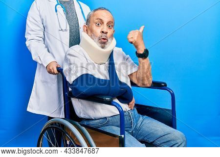 Handsome senior man with beard sitting on wheelchair with neck collar surprised pointing with hand finger to the side, open mouth amazed expression.