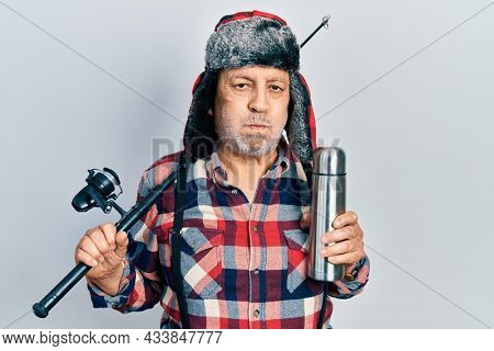 Handsome mature man wearing fisherman equipment and thermo puffing cheeks with funny face. mouth inflated with air, catching air.