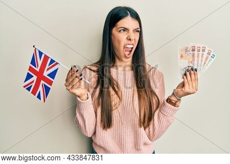Young hispanic woman holding united kingdom flag and pounds banknotes angry and mad screaming frustrated and furious, shouting with anger. rage and aggressive concept.