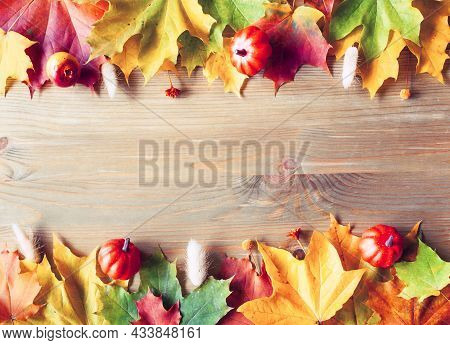 Thanksgiving background. Autumn Thanksgiving background. Maple autumn leaves on the wooden background with free space for text, vintage tones processing. Thanksgiving border, Thanksgiving frame, Thanksgiving festive card, Thanksgiving festive background