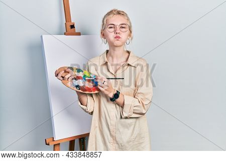 Beautiful caucasian woman with blond hair standing drawing with palette by painter easel stand puffing cheeks with funny face. mouth inflated with air, catching air.