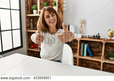 Young caucasian girl wearing casual clothes sitting on the table at home approving doing positive gesture with hand, thumbs up smiling and happy for success. winner gesture.