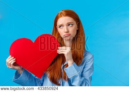 Gloomy Girl Was Rejected On Valentines Day. Uneasy Upset Redhead Female In Nightwear, Holding Heart
