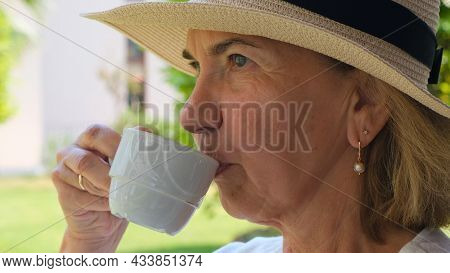 Dreamer An Adult Female Aged 50-55 In A Straw Hat Drinks A Hot Drink Of Coffee Or Tea From A White C