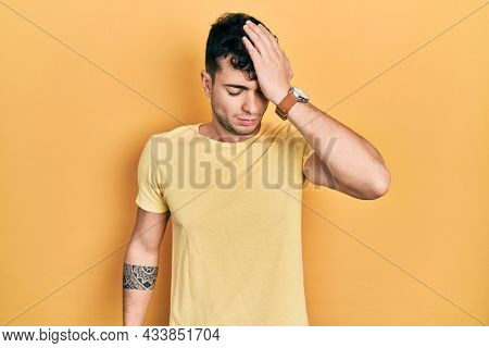 Young hispanic man wearing casual t shirt surprised with hand on head for mistake, remember error. forgot, bad memory concept.