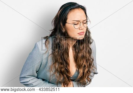 Young hispanic girl wearing business clothes and glasses with hand on stomach because indigestion, painful illness feeling unwell. ache concept.