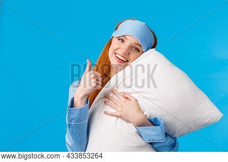 Saying Yes To Good Healthy Sleep. Cheerful Pretty Redhead Woman In Sleep Mask And Nightwear, Hugging