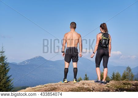Rear View Of Sporty Man And Woman Standing On Top Of Rock And Admiring Beautiful Scenery Of Mountain
