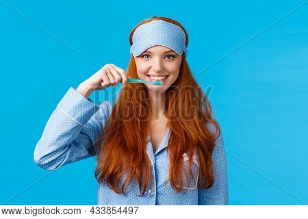 Habits, Hygiene And Lifestyle Concept. Cute Feminine Redhead European Woman In Nightwear, Sleep Mask