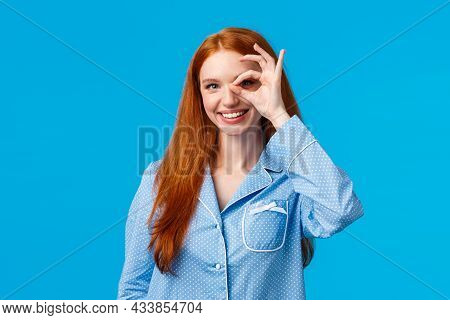 Excellent Choice Right Here. Charismatic Satisfied Redhead Female In Nightwear Showing Okay Gesture,