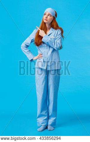 Uneasy And Worried, Concerned Upset Redhead Female In Nightwear And Sleep Mask, Looking Pointing Upp