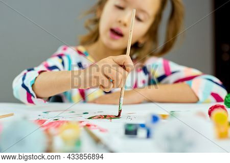 Cute Child Sitting At The Table And Drawing Red Heart On White Paper