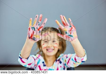 Little Girl With Painted Colorful Watercolor Hands Up, Child Sitting At The Table And Drawing,
