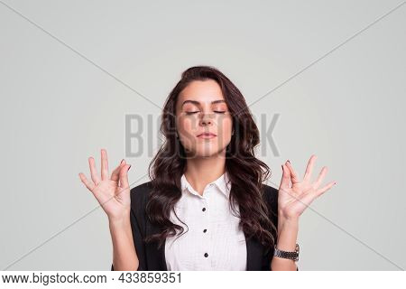 Tranquil Adult Business Lady With Eyes Closed And Mudra Fingers Meditating For Stress Relief Against