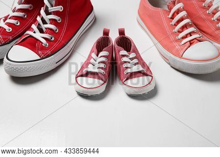Stylish Sneakers For All Family Members On White Wooden Background