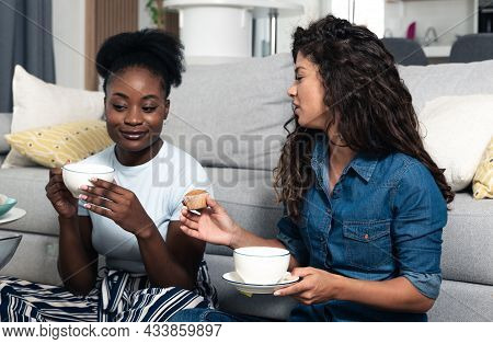 Two Young Woman One African Black Other White Sitting On The Floor In The Apartment Drinking Cup Of