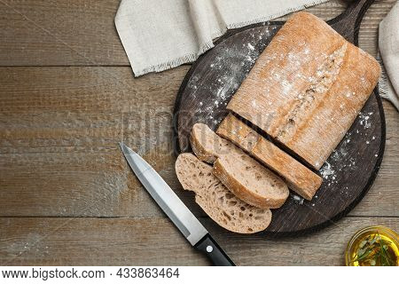 Cut Delicious Ciabatta On Wooden Table, Flat Lay. Space For Text