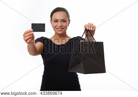 Beautiful Mixed Race Woman Looks At Camera And Smiles Toothy Smile, Showing Black Shopping Packet An
