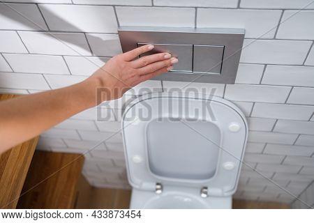 Female Hand Presses Toilet Flush Button Closeup