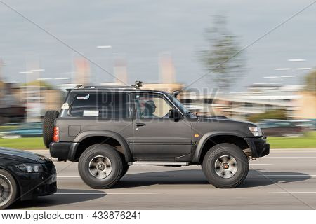 Nissan Patrol Rebuilt For Off-road Use. A Black Suv Is Driving Down The Street. Motion Blur. Riga, L