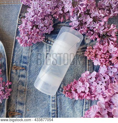 Mock Up Of Transparent Bottle Of Intimate Lubricant Gel And Fragrant Fresh Lilac On A Denim Backgrou
