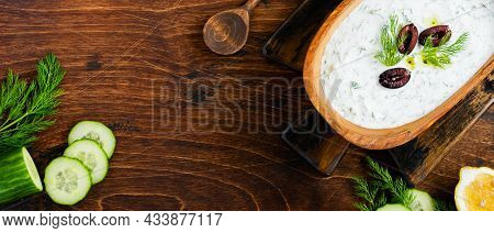 Traditional Greek Sauce Tzatziki In Olive Wooden Bowl On Old Rustic Background. Top View.