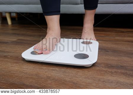 Close-up Female Feet Stepping On Body Weight Scale. Weight Control, Weight Loss Concept.