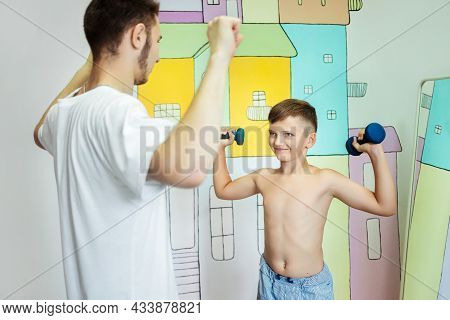 Boy Trains With A Physiotherapist With Dumbbells In A Rehabilitation Center. Smiling Child With Rais