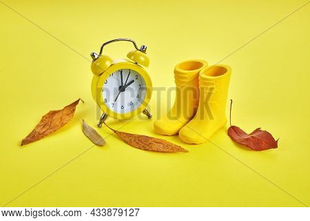 Fall Back Daylight Saving Time Concept With Yellow Clock, Boots And Autumn Leaves On Yellow Backgrou