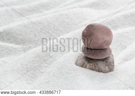 Stacked zen stones sand background in art of balance concept