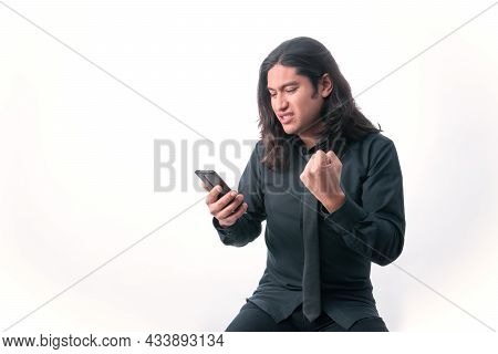 Person With White Background. He Is Looking At His Smart Phone. He Is Angry About Something He Has S