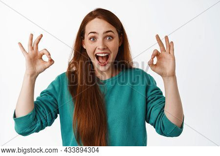Excited Girl With Red Hair, Shows Okay Ok Gesture, Praise Super Cool Event, Smiling Amazed And Happy