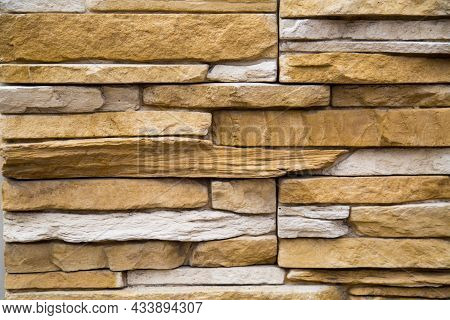 The Background Of The Wall Is Made Of Artificial Stone Of An Elongated Irregular Shape In Gray And B