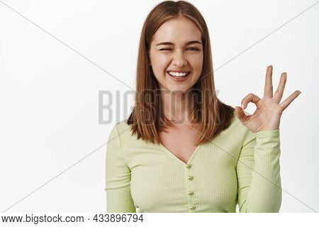 Yes, Alright. Happy Smiling Woman Guarantee Quality, Shows Okay Ok Zero Sign, Winking And Look Satis