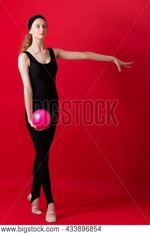 Graceful Slim Girl In Black Leotard Doing Gymnastics. Full Length Portrait Of Beautiful Athlete Girl