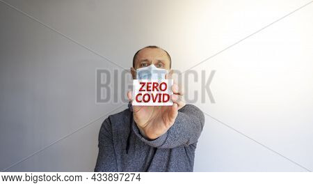 Covid-19 Zero Covid Symbol. White Card, Words Zero Covid. A Young Man In A Grey Wear And Medical Mas