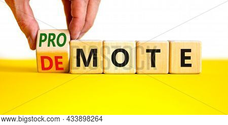 Promote Or Demote Symbol. Businessman Turns A Cube And Changes The Word 'demote' To 'promote'. Beaut