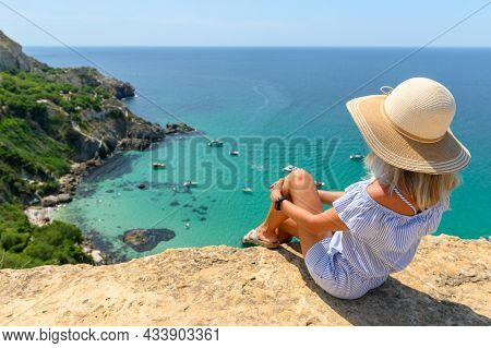 A Young Girl In A Straw Hat Sits On The Edge Of A Cliff And Looks At The Beautiful Seascape With Yac