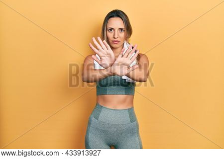 Beautiful hispanic woman wearing sportswear and towel rejection expression crossing arms doing negative sign, angry face