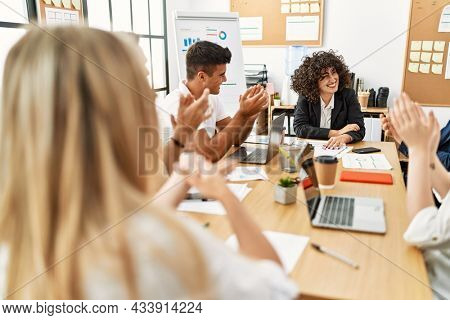 Group of young business workers smiling and clapping to partner at the office.
