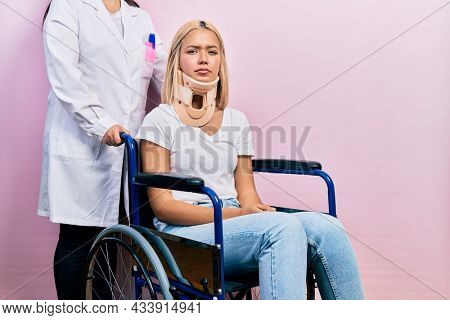 Beautiful blonde woman sitting on wheelchair with collar neck depressed and worry for distress, crying angry and afraid. sad expression.