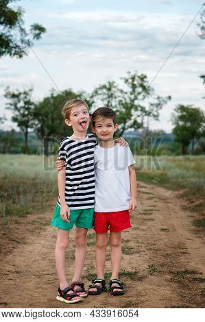 Two Happy Little Kids Boys Embracing In Rural Settings. Older Brother Shows Tongue. Funny Children,