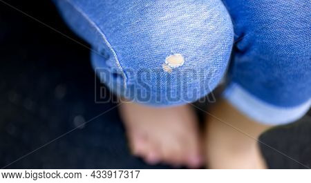 Blue Jeans With Holes Sitting On The Black Background And Copy Space.