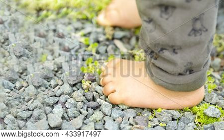 Close Up Of The Bare Foot Of The Child Walking On Over Gravel And Copy Space.