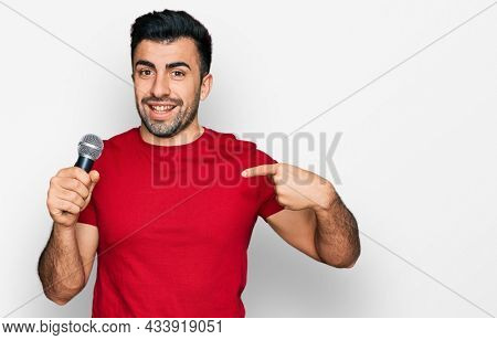 Hispanic man with beard singing song using microphone pointing finger to one self smiling happy and proud