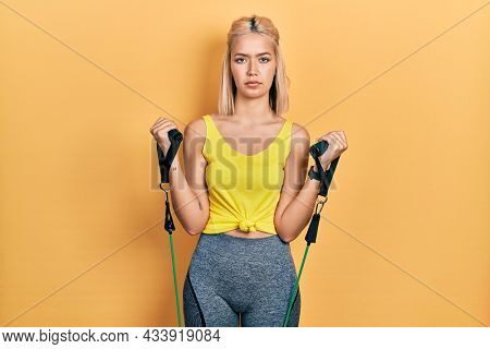 Beautiful blonde woman training arm resistance with elastic arm bands relaxed with serious expression on face. simple and natural looking at the camera.