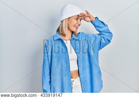 Beautiful blonde woman wearing wool hat very happy and smiling looking far away with hand over head. searching concept.