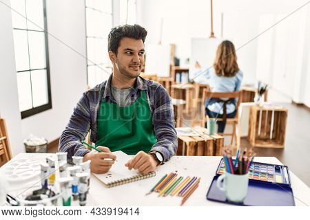 Young artist man at art studio smiling looking to the side and staring away thinking.