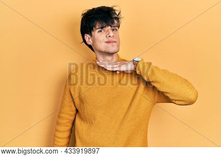 Handsome hipster young man wearing casual yellow sweater cutting throat with hand as knife, threaten aggression with furious violence